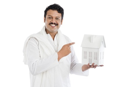 kurta: Portrait of a smiling man pointing at a model home Stock Photo