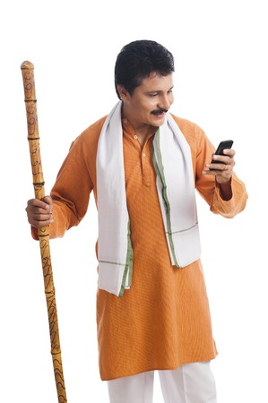 Close-up of a man holding a wooden staff and using a mobile phone