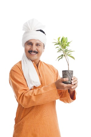 Portrait of a farmer holding a potted plant and smiling Banque d'images