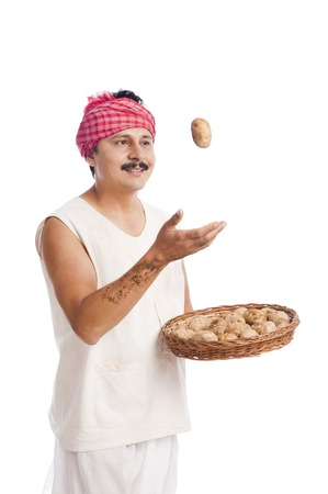 dhoti: Farmer tossing a potato from the basket Stock Photo