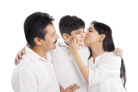 Close-up of a couple kissing their son photo