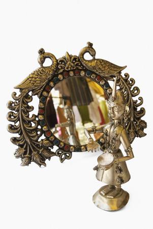 metal sculpture: Antica scultura in metallo di fronte a uno specchio decorativo