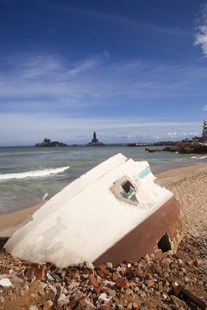 Rubbles of a building on the beach with Thiruvalluvar Statue , Kanyakumari, Tamil Nadu, India Standard-Bild