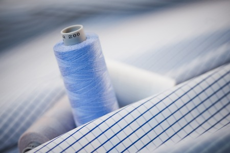 textile image: Close-up of spools of thread on a fabric Stock Photo