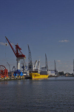ships with cranes in the harbor of rotterdam netherlands photo