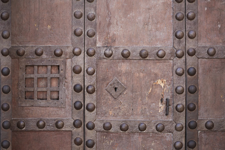 peephole: An ancient wooden door detail; peephole and nails Stock Photo