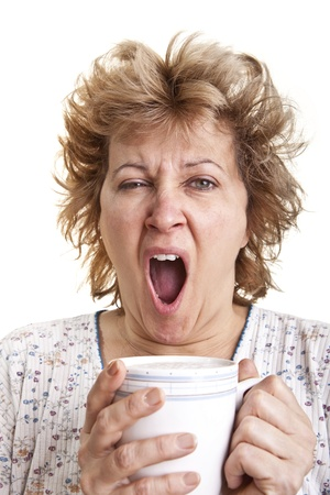 fatigued: Woman waking up with a coffee Yawning Stock Photo