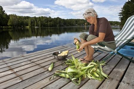 beach front: Woman shucking corn by a lake