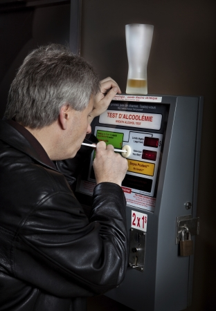 intoxicated: Man taking breathalyzer test at a bar