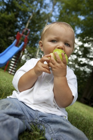 Young boy eating a green apple at the park  photo