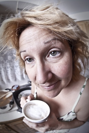 bad hair day: Woman waking up with a coffee (Dirty dishes fisheye)  Stock Photo