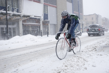 Bicycle courier in winter snow storm  Imagens
