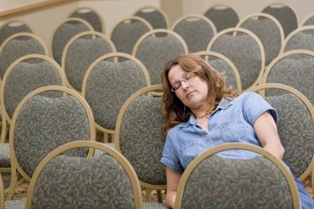 Woman sleeping at boring conference  Imagens