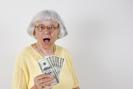 us money: Shocked senior woman holding lots of cash