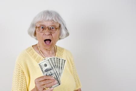 giving money: Shocked senior woman holding lots of cash