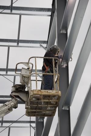 soldador: Soldador de vigas de acero de soldadura en el sitio de construcción