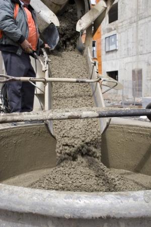 mezclador: Operador de cami�n vertiendo cemento en bote de gr�a  Foto de archivo
