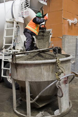 mixer: Truck operator pouring cement into crane bucket
