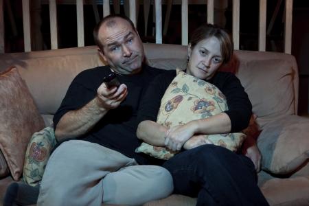 Bored couple watching TV  Imagens