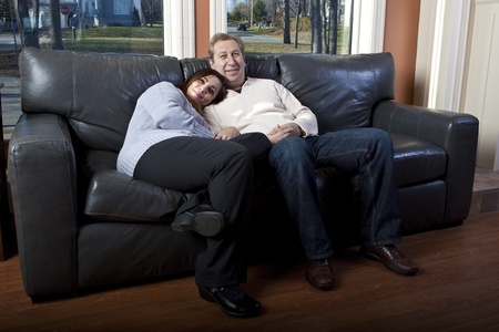 Happy couple sitting on a couch Stock Photo - 10522514