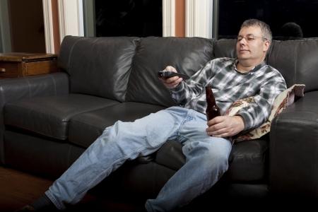 sedentario: Couch potato viendo la televisión y beber cerveza  Foto de archivo