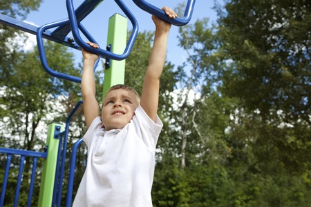 school playground: Boy playing on monkey bars