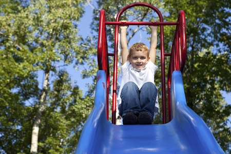 children at play: Boy Playing on a slide at the park