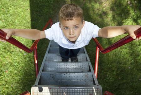 niño escalando: Chico una diapositiva en un parque de escalada