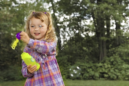 playing field: Young girl blowing soap bubbles
