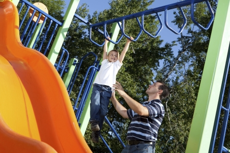 Father and son playing on monkey bars at the park