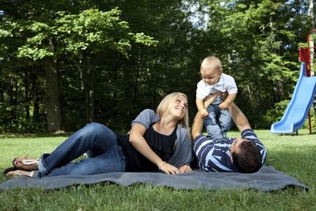 若い家族 (男の子だけ) の公園で遊ぶ
