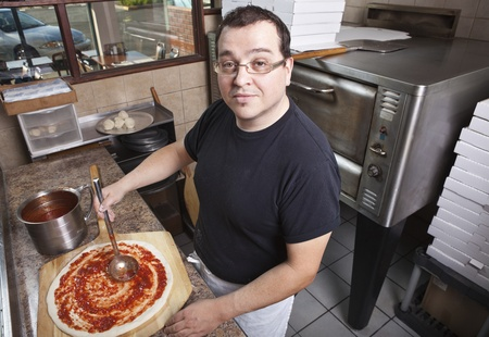 busy restaurant: Chef making a pizza spreading sauce