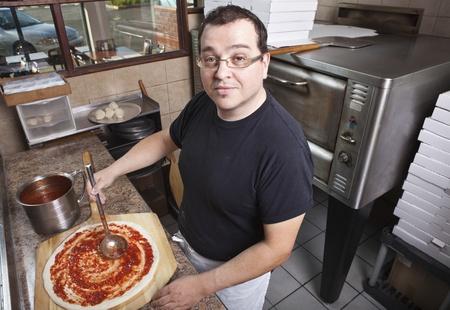 negocios comida: Cocinero haciendo una pizza propagando salsa