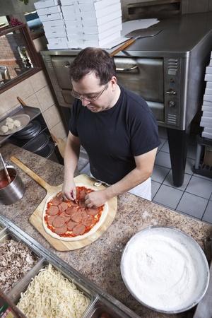 negocios comida: Cocinero haciendo una pizza