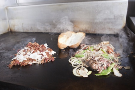 griddle: Griddle with Steak and Peperoni Submarine Sandwich and Bacon Mushrooms