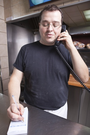 minimum wage: Restaurant owner writing take out order while on the phone  Stock Photo