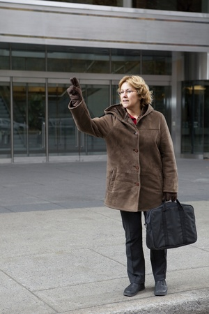 hailing: Outdoor business woman hailing a taxi cab  Stock Photo