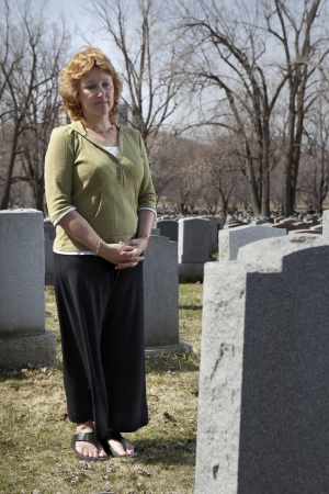 somber: Grieving widow in front of cemetery tombstone