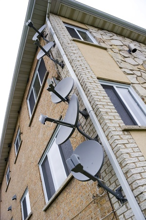 unsightly: Many satellite dishes on side of apartment building
