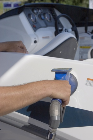 fueling: Man filling his boat with fuel at a gas station