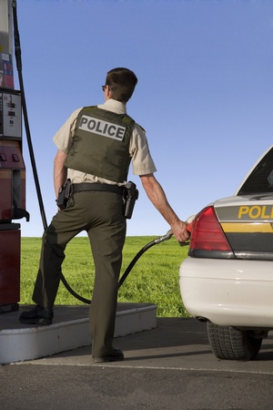 Policeman pumping gas  Stock Photo - 10555314