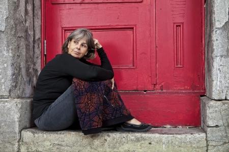 Frau sitzt auf Tür bücken