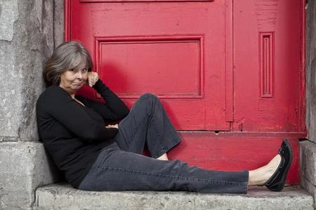 ドア猫背に座っている女性 写真素材