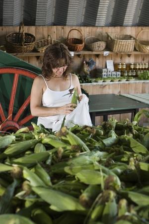 トウモロコシ、農民市場での買物の女性