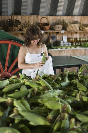 grocer: Woman shopping for corn at the farmers market