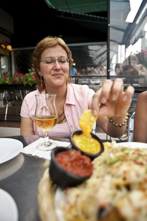 mature mexican: Woman enjoying Nachos and Beer at an Outdoor Cafe  Stock Photo