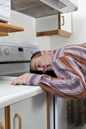 Exhausted man asleep in a frying pan  photo