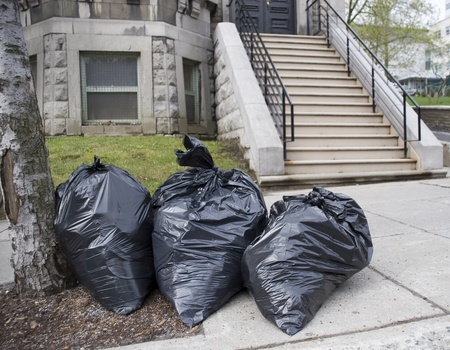 Bags of trash on sidewalk in front of townhouse  Stock Photo