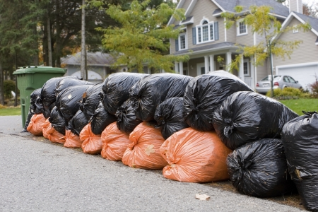 Many orange and green garbage bags at curb  Stockfoto