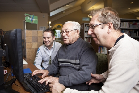 community service: Volunteers teaching a senior how to use a computer